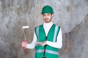 engineer-man-yellow-uniform-helmet-holding-trim-roller-wall-painting (1)
